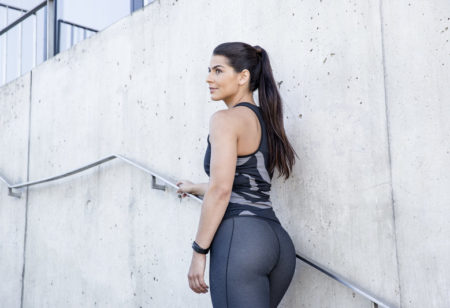 Image from behind of a young woman standing on stairs outside.
