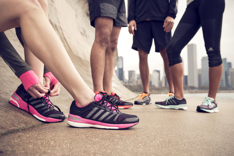 A close up of 4 people in adidas running shoes