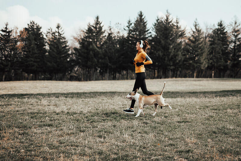 A young lady with her dog running