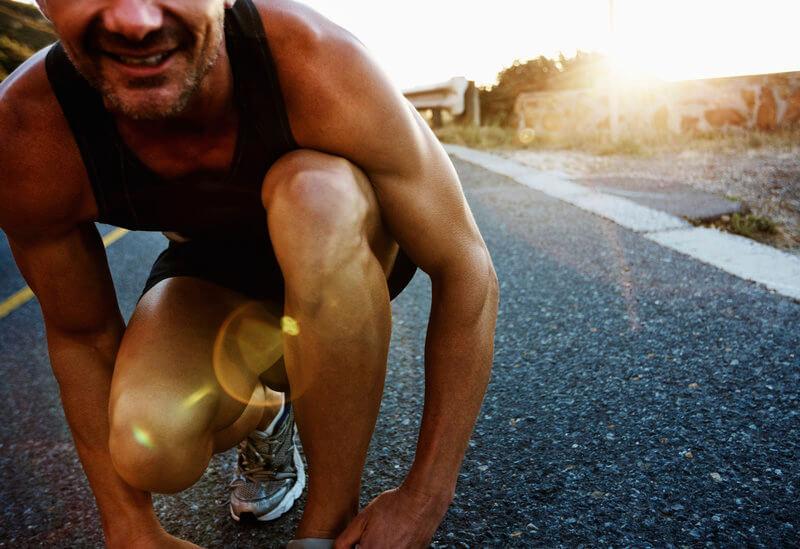 Athletischer Laeufer bindet seine Schnuersenkel.