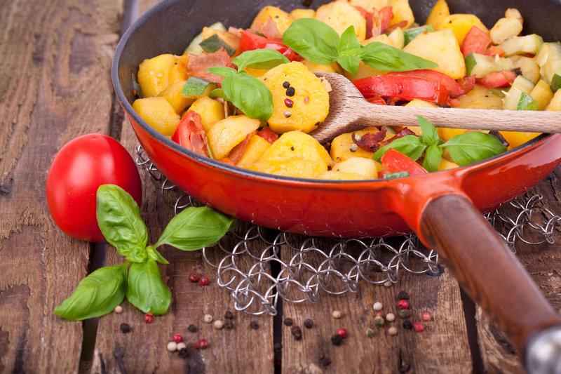 Potatos and vegetables in a pan.