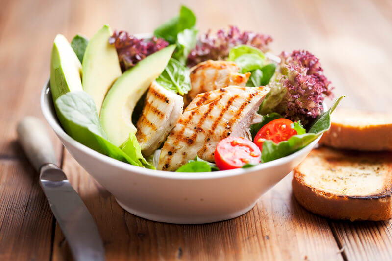 Chicken salad with avocado and fresh vegetables.