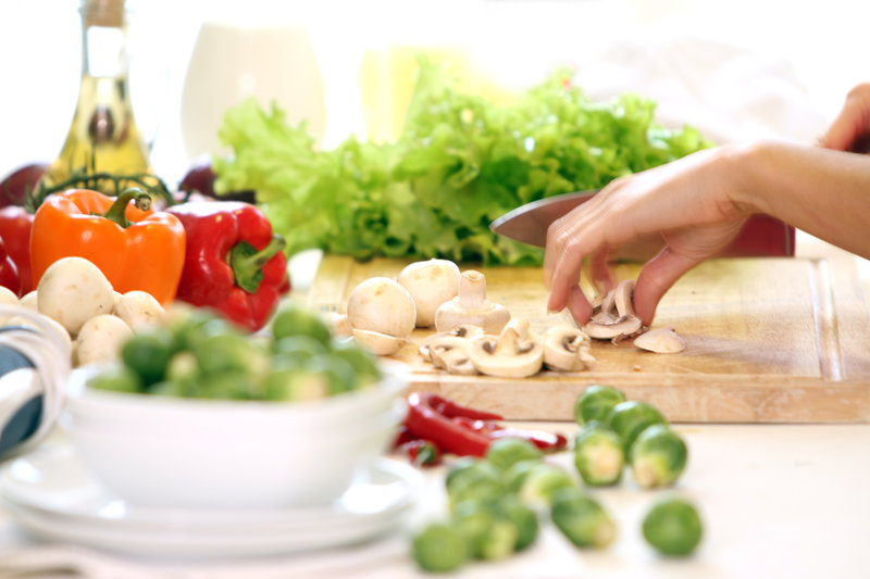 Woman is cutting fresh vegetables on a wooden plate.