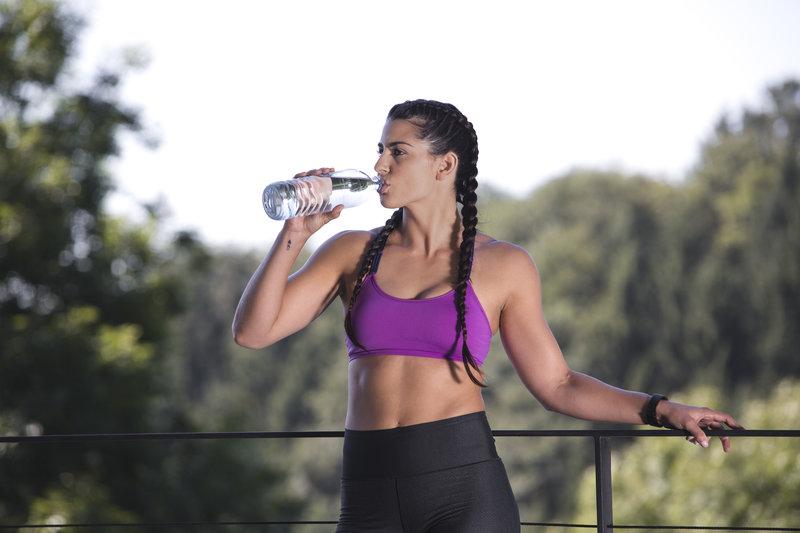 Sportliche Frau trinkt aus ihrer Wasserflasche.