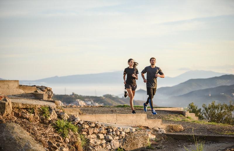 Ein Mann und eine Frau laufen auf den Bergen
