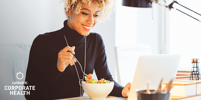 Woman sitting in front of her laptop and eating a salad