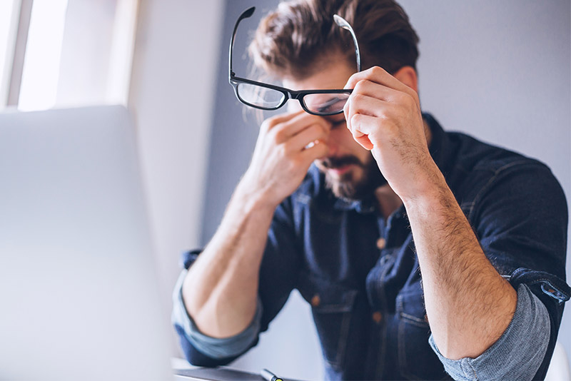 Man sitting in front of his laptop rubbing his eyes