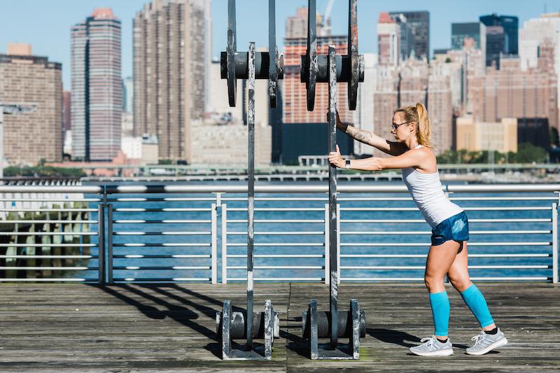 Eine junge Frau an einer Kraftbank vor der New Yorker Skyline