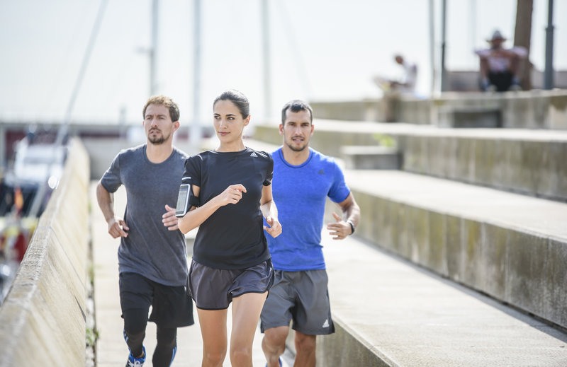 A woman and two men running in the city