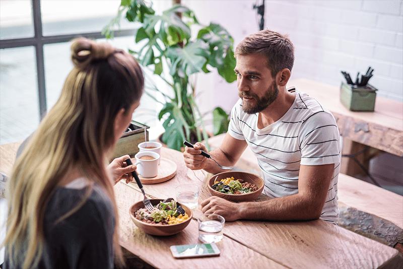Ein Mann und eine Frau sitzen am Tisch und essen