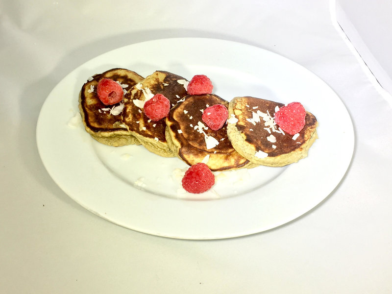 A plate with pancakes and raspberries on top