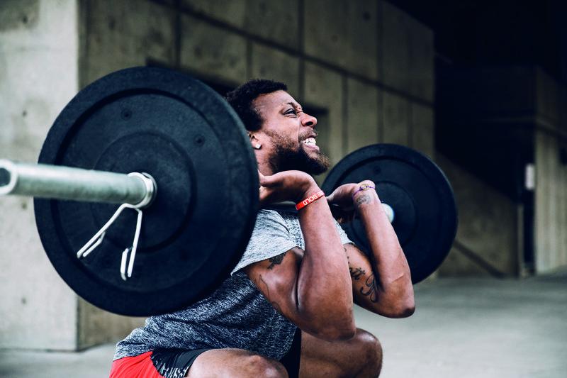 Homem fazendo agachamento com peso