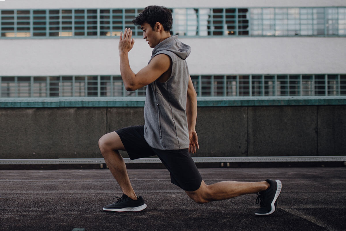 A young guy is doing walking lunges after a run