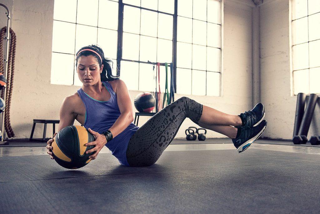 Athletische Frau macht Sit-ups mit einem Medizinball.