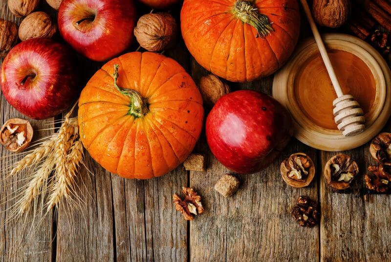 Foto von Kuerbissen, Aepfeln, Walnuessen und Honig auf einem Holztisch.