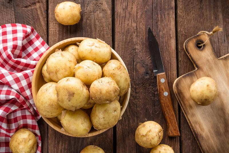 Eine Schüssel Kartoffeln auf einem Holztisch
