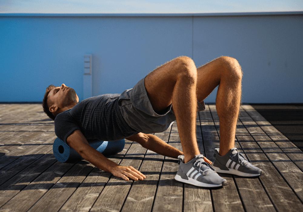 Homem massageando a parte superior das costas com o foam roller