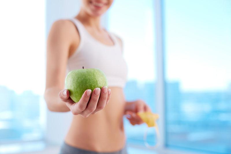 Junge Frau im Sportoutfit haelt einen gruenen Apfel in der Hand