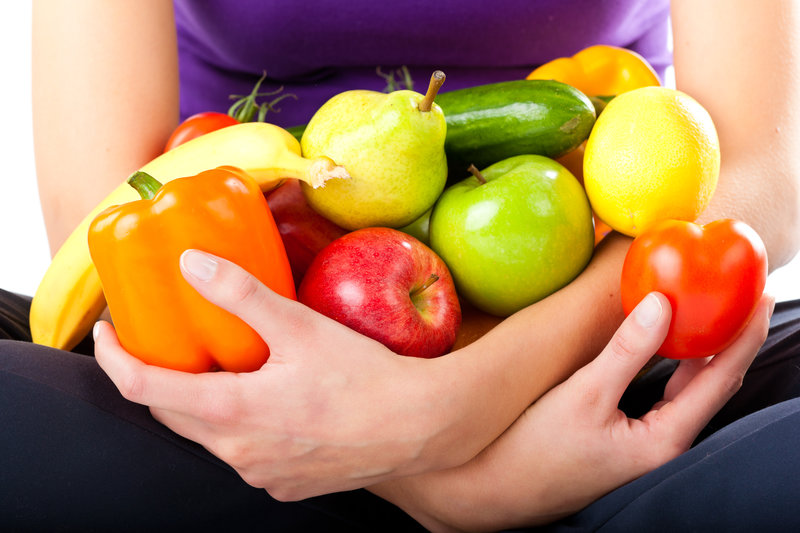 woman sitting on the ground holding different kinds of fruits in her arms