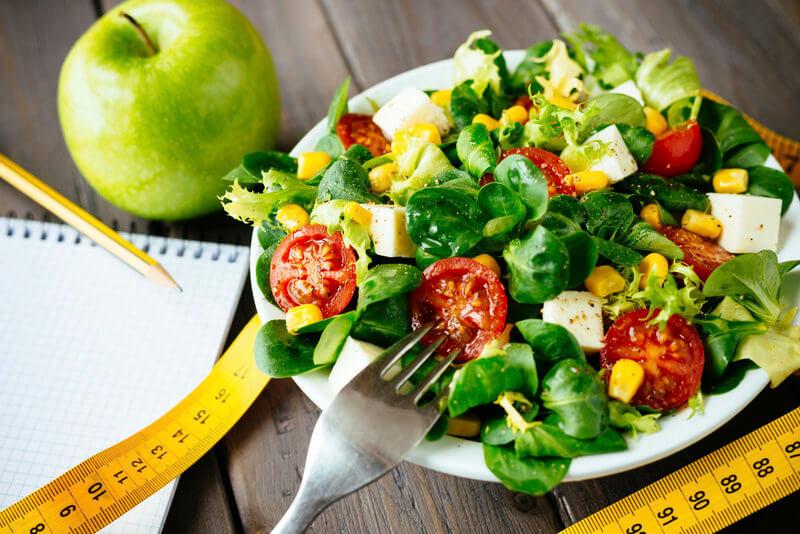 Bild von einem gemischten Salat, einem Apfel, einem Maßband und einem Schreibblock.