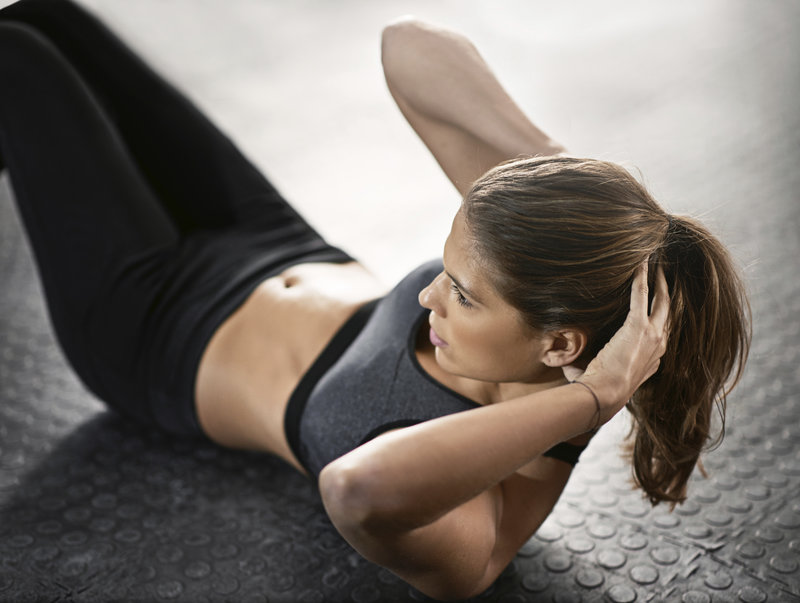 Beautiful woman doing a sit up to the side on a fitness mat.