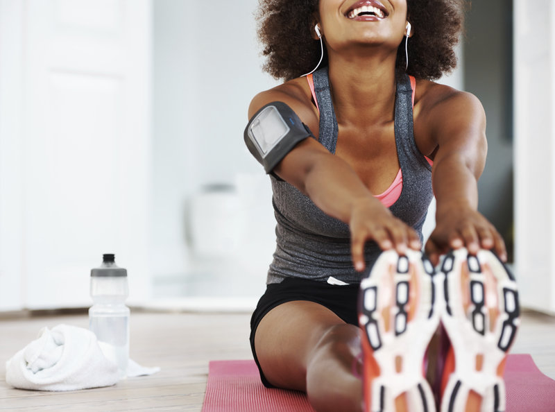 A fit smiling african american woman in gym clothing sitting on an exercise mat on her living room floor and stretching out her legs.