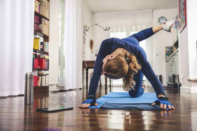 Woman at home is doing a workout on the floor.