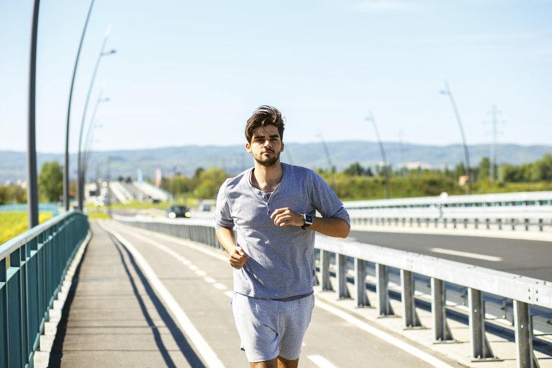 Young man running over a bridge.