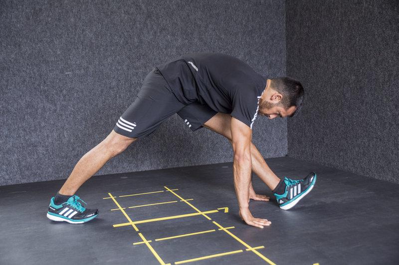 Athletischer Mann macht einen Ausfallschritt nach vorne mit folgendem Adduktoren- und Hamstring-Stretch.