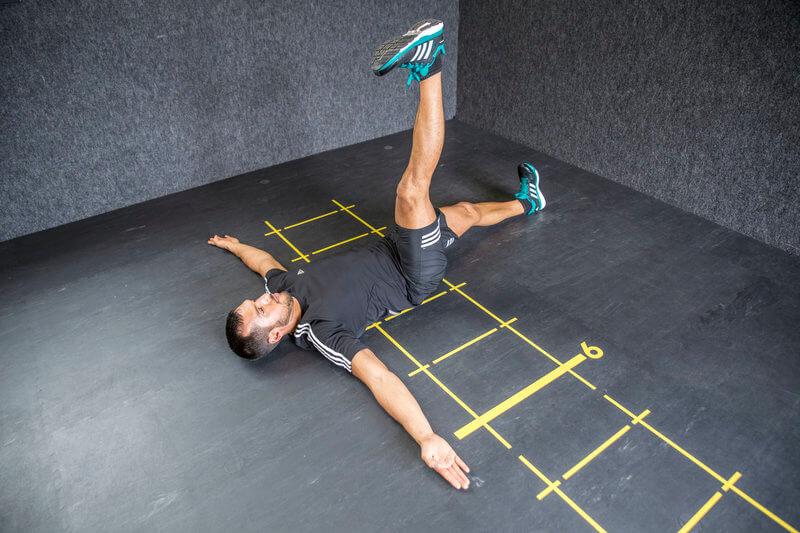 Athletischer Mann macht einen Skorpion in Rückenage.