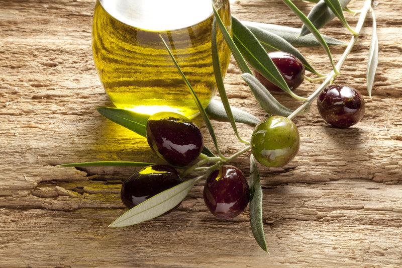 Ein Glas gefüllt mit Oliven-Öl und rundherum liegen frische Oliven.