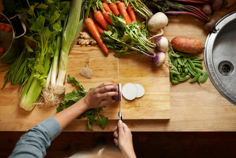 Man sieht zwei Hände die frisches Gemüse schneiden, welches auf einer Holzplatte liegt.