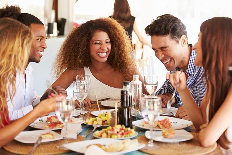 Grupo de amigos comiendo y riendo