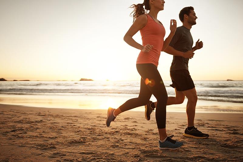Young couple running on the beach in Rio de Janeiro.