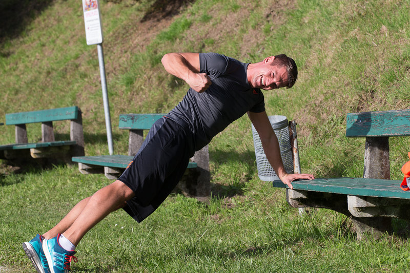 Young man doing high planks outside.