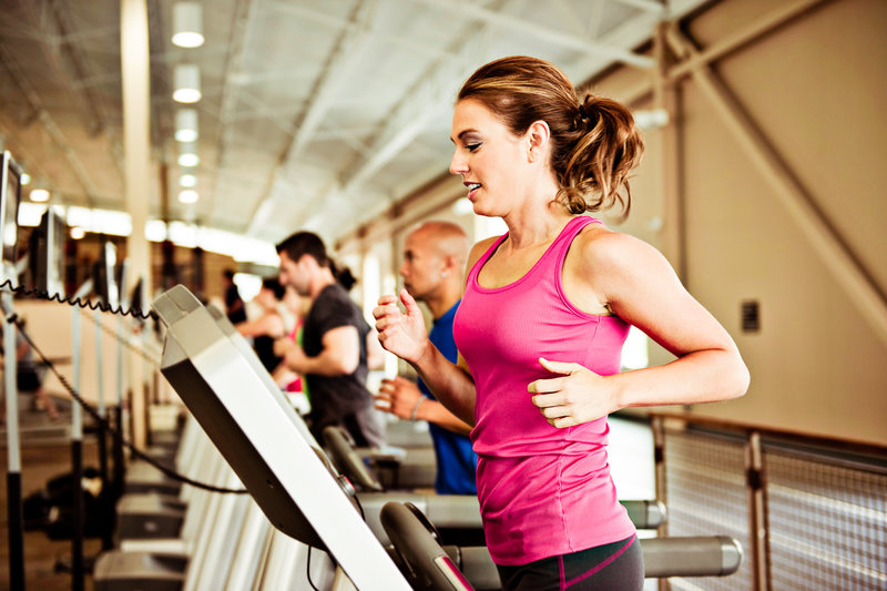 Young woman running on a treadmill.