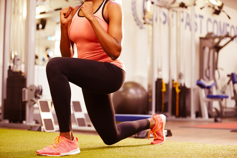 Sportliche Frau mach Lunges im Fitnessstudio.
