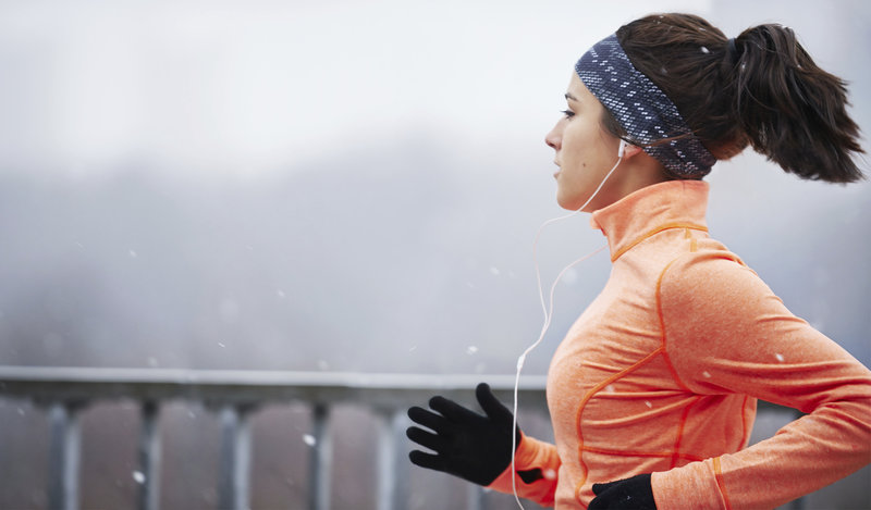Young woman running in winter.