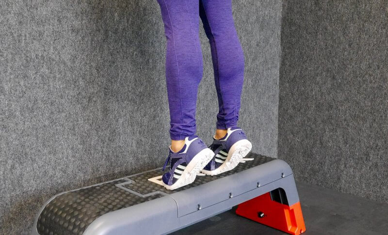 Woman doing eccentric strengthening exercises for her calfs.