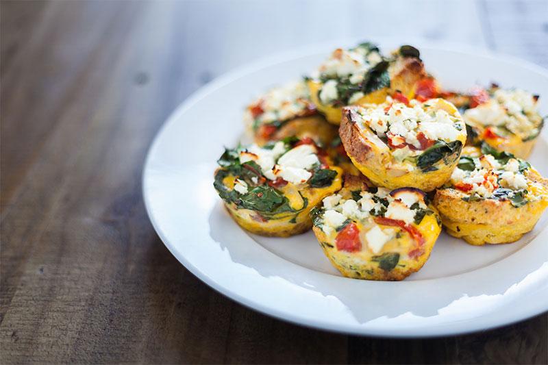 Um prato contendo muffins de ovo, queijo e legumes
