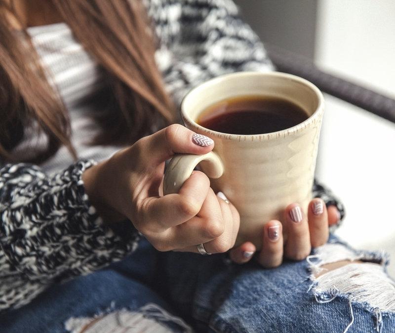 Junge Frau haelt einen Kaffee in ihren Haenden.
