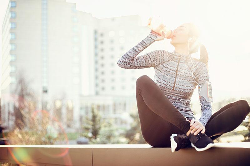 Junge Frau sitzt auf einer Bank und trinkt einen Protein Shake nach dem Training.
