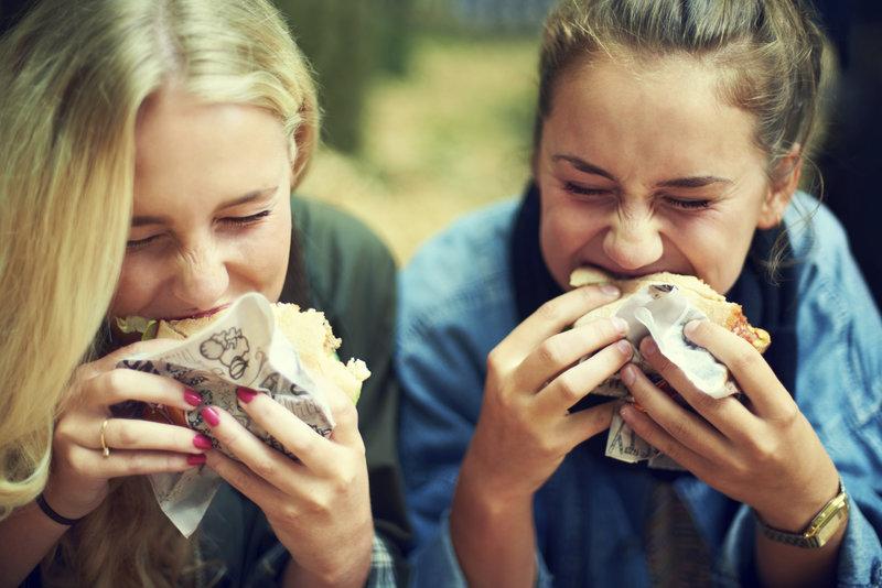 Zwei gunge Maedchen essen einen ungesunden Buerger.