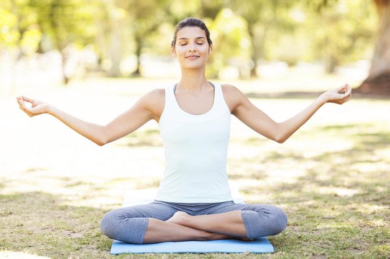 Junge Frau im Freien in einer Yogapose.