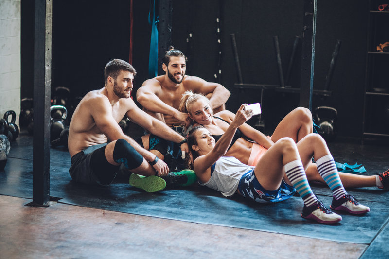 Group of healthy people resting in gym after hard cross training and making selfie.