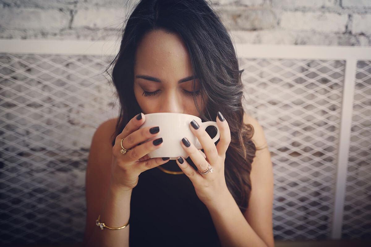 Eine junge Frau trinkt eine Tasse Kaffee