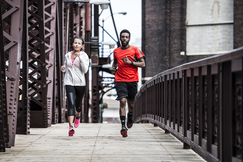 Hombre y mujer corriendo en un puente