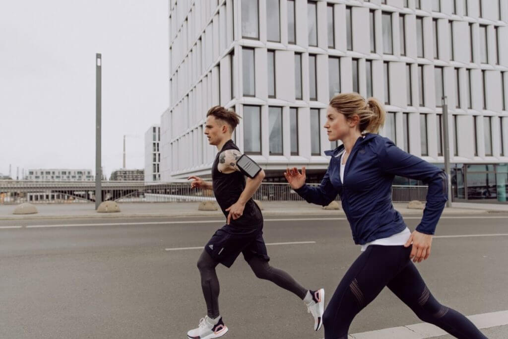 A man and a woman running in the city