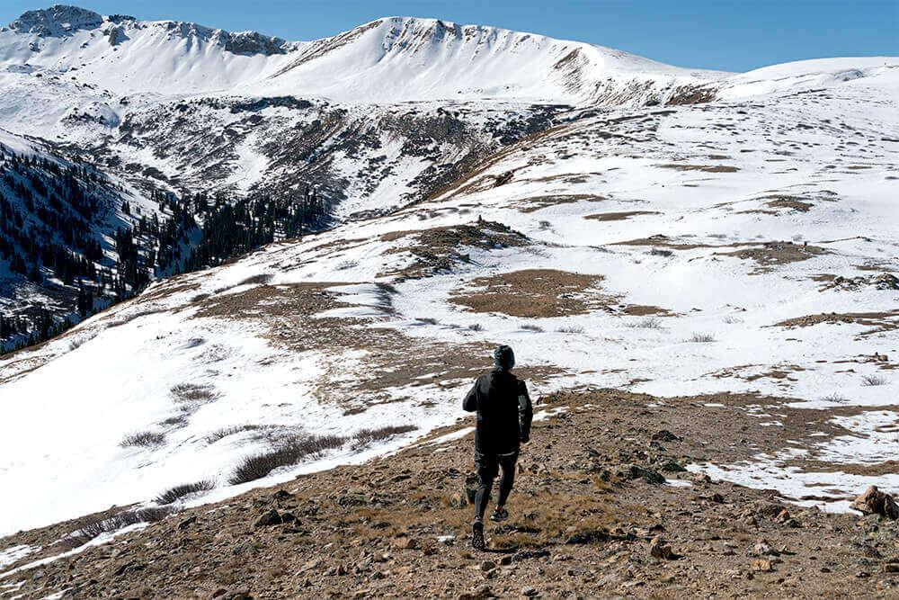 Homem correndo em trilha em montanha nevada