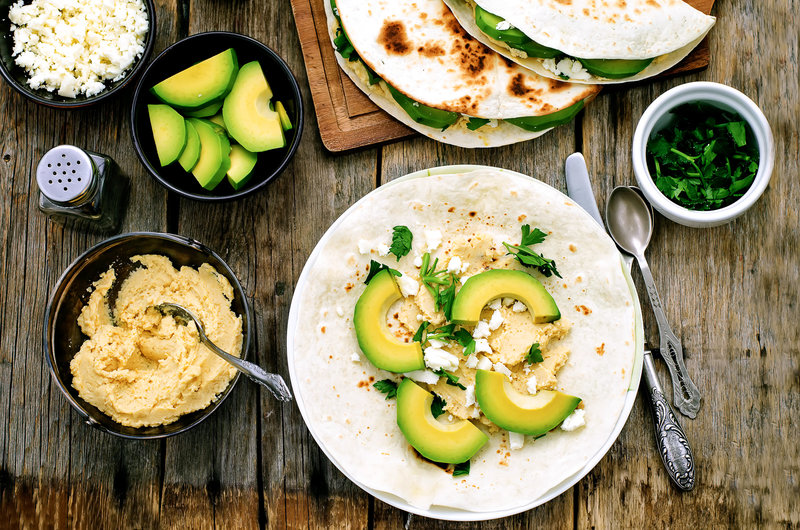tortilla avec houmous, avocat, feta et persil sur une table